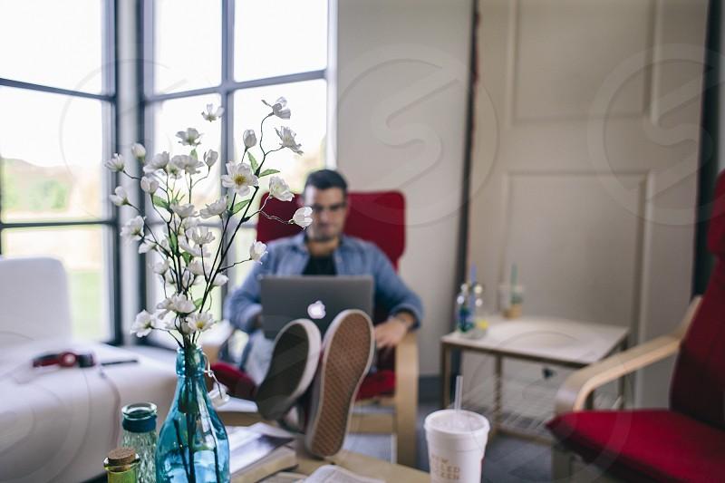man sitting using his laptop photo