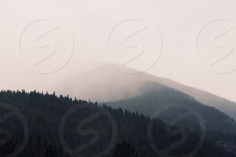 black rolling mountain with clouds photo