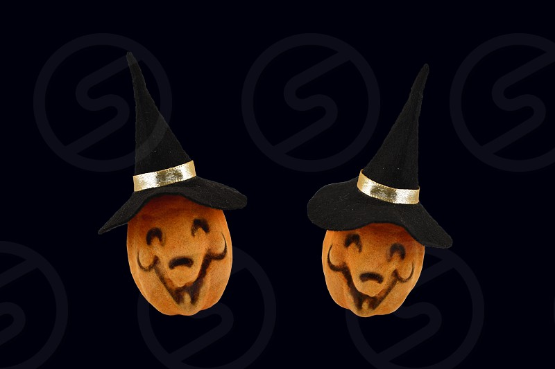 Two Halloween Pumpkins. Haloween pumpkin isolated on a black background. Pumpkin with a witch hat photo
