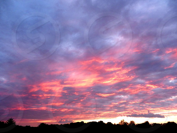 Sunset of fiery bloody clouds hanging over a forest horizon in silhouette photo