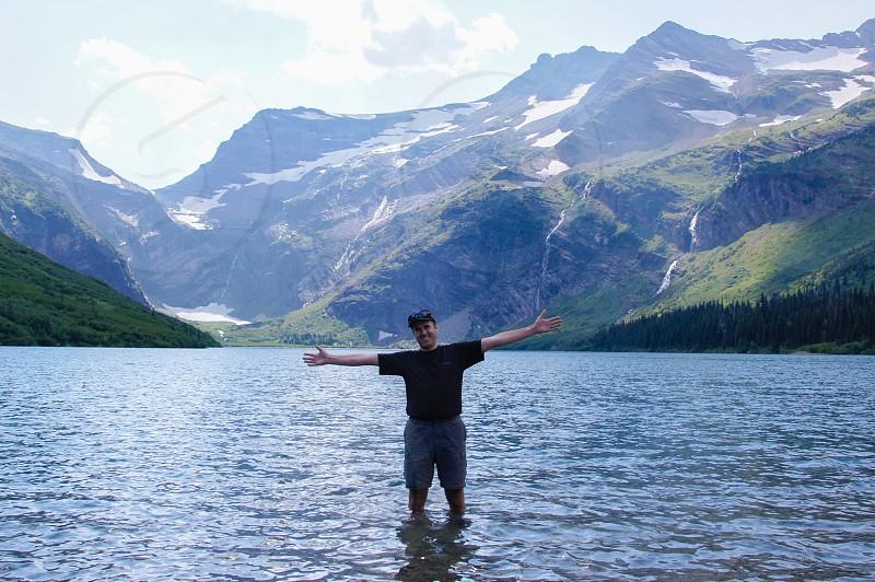 Lake man mountains standing water wading photo