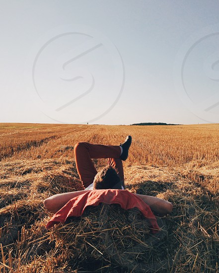 person lying on brown haystack field photo