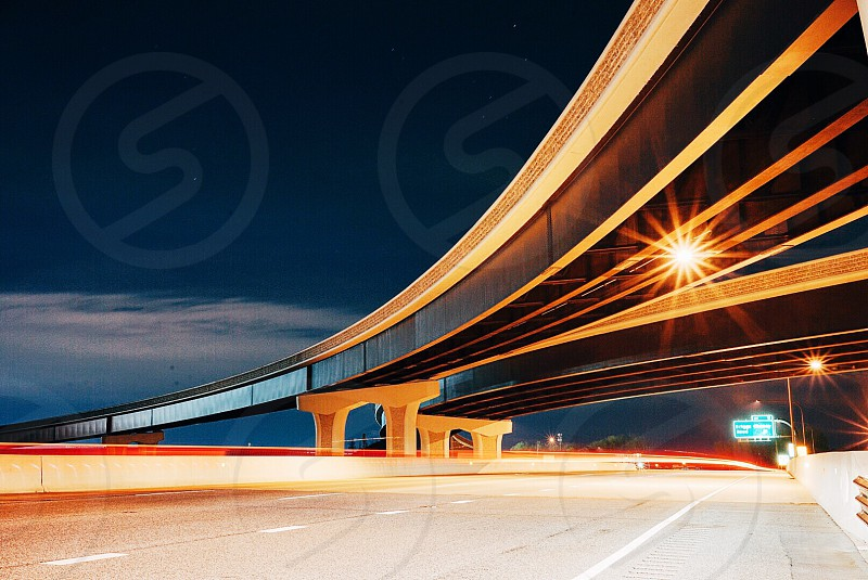 gray and black concrete vehicle bridge with street lights during night time photo