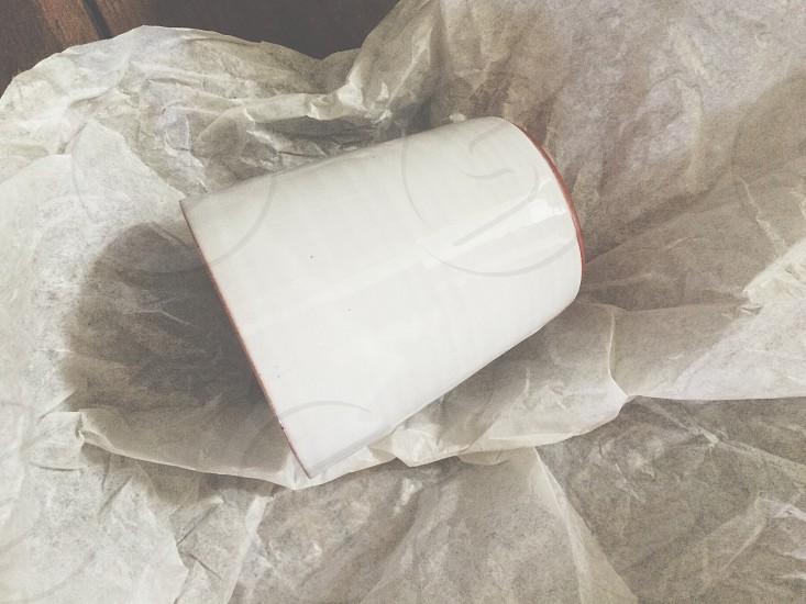 white ceramic mug on white textile photo