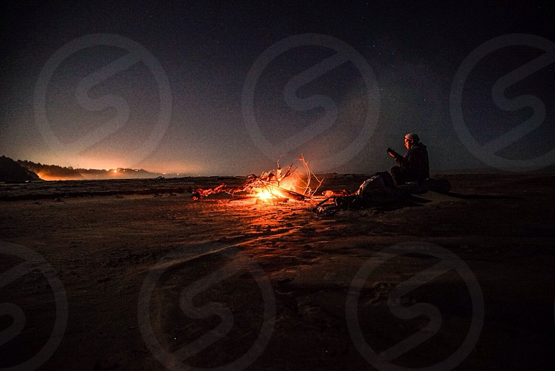 man in black jacket and pants with beanie in front of a burn fire photo