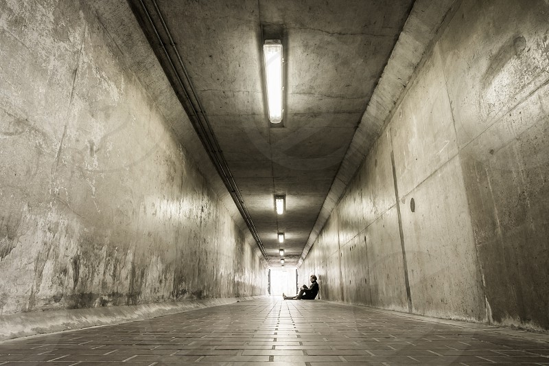 Man sitting down in a foot tunnel looking content photo