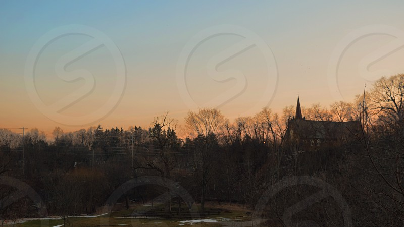 silhouette of a church and trees in the background of a sunset photo
