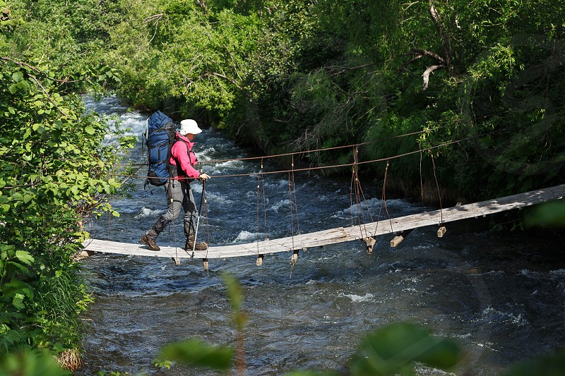 KAMCHATKA PENINSULA RUSSIA - JULY 11 2014: Summer hiking on Kamchatka - young woman hiker with backpack behind her shoulders crossing mountain river on pedestrian suspension bridge in summer forest. photo