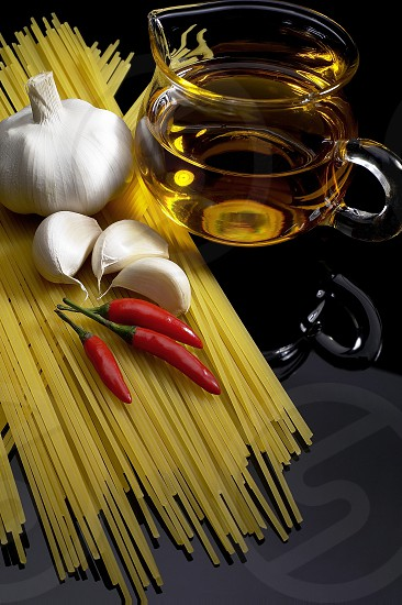 pasta garlic olive oil and red chili pepper ove black reflective surface photo