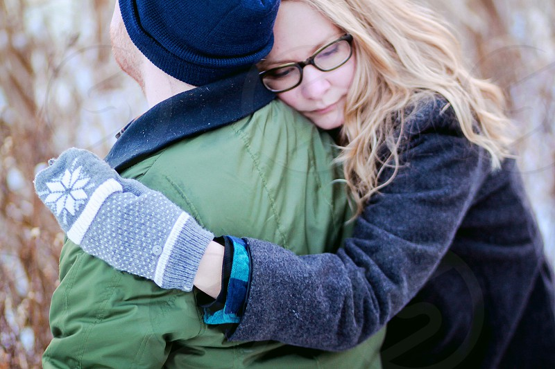woman in blue jacket hugging a man in green and blue jacket photo