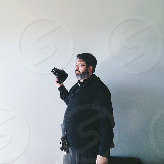 man in black jacket holding a black dslr cameraa photo