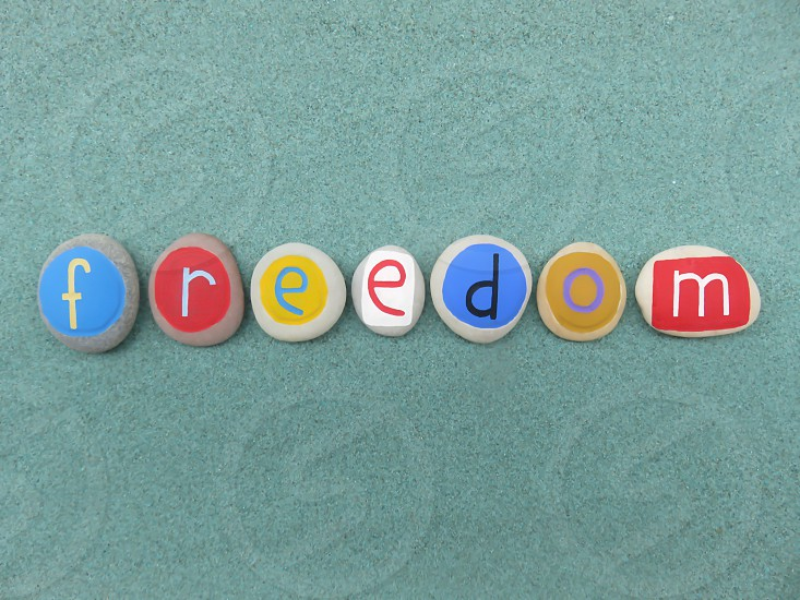 Freedom word composed with carved and colored pebble stones over green sand                       photo