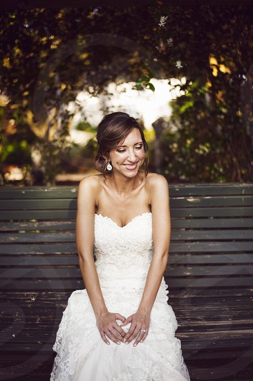 bride wearing a white strapless lace dress smiling and sitting on a park bench photo