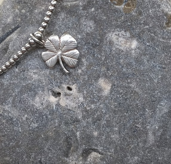 silver clover pendant silver necklace on rock during daytime photo