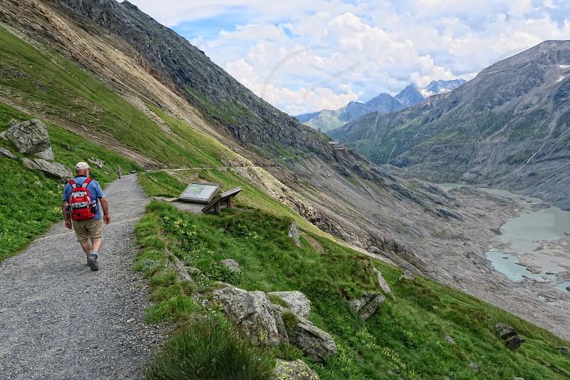 Grossglockner SALZBURGER LAND/ AUSTRIA July 30 2016: hiker walking along a path at Grossglockner Mountain and Pasterze in Austria. Summer. photo