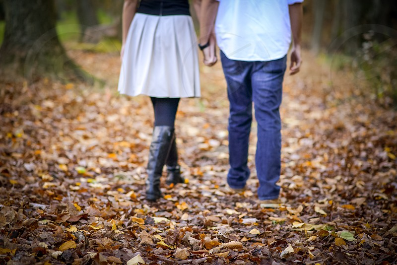 couple on field surrounded with leaves photo
