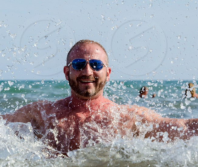 Young man with beard wearing sunglasses looking at the camera smiling. In the sea with water splashing. High shutter speed water droplets look frozen. Model release available.  photo