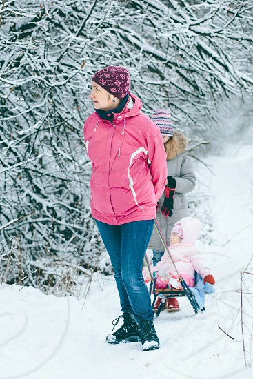 Woman pulling sledge with her little daughter during a walk in the forest photo