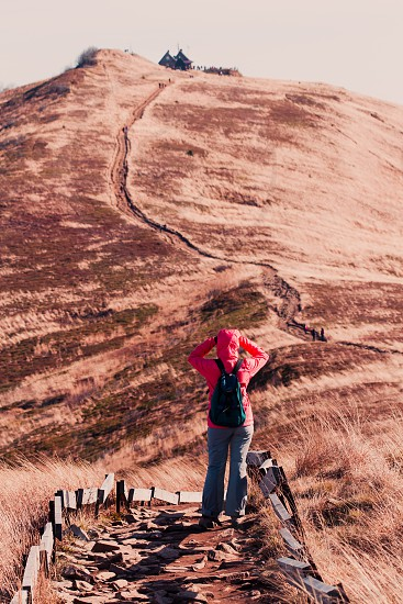 Woman walking along mountain path admiring mountains scenery during a trip on sunny windy autumn day. Hiker wearing sports clothes and shoes carrying backpack on her back. There is grassy hillside coloured with browns around footpath in fall season photo