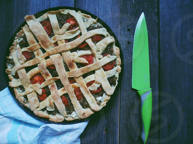 baked pie beside green kitchen knife on brown wooden table photo