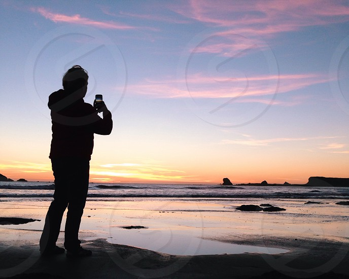 man taking picture in the sea silhouette  photo