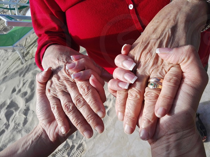 couple holding hand on sand field during daytime photo