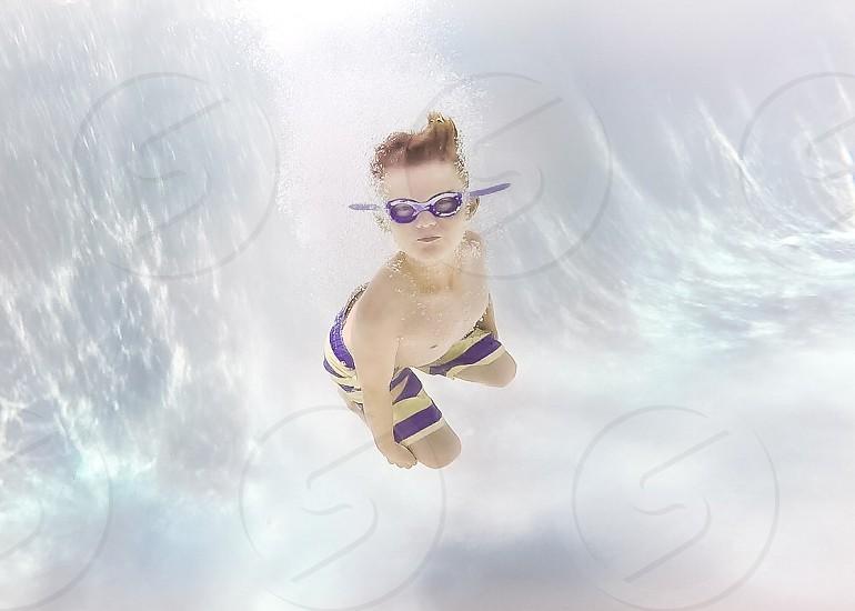 Boy swimming underwater cannonball  photo