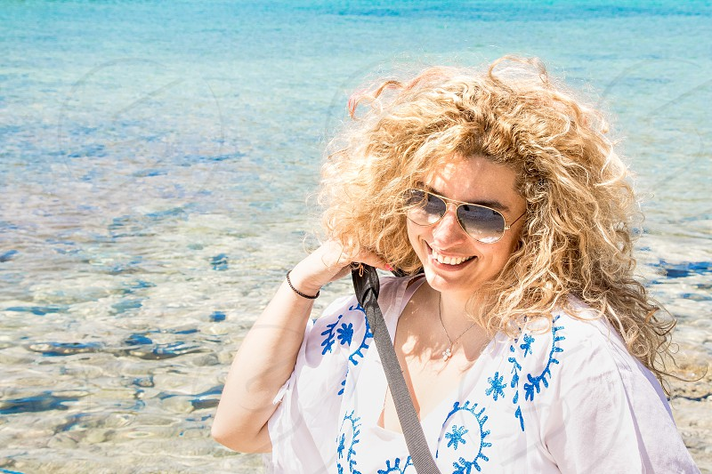 woman wearing blue printed white scoop neck shirt and gold framed aviator sunglasses with crossbody bag put on her having background of clear blue ocean photo