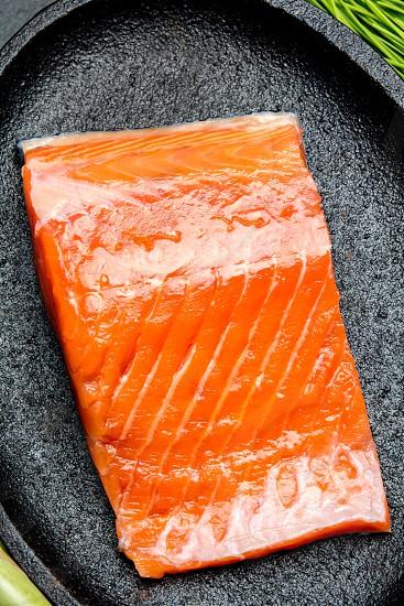 Raw salmon filet on black iron plate. Top view. photo