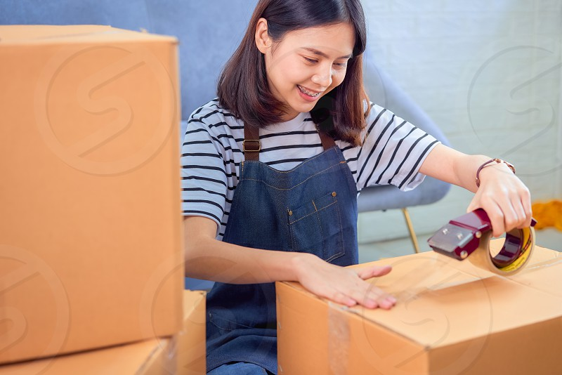 Startup small business concept young Asian woman owner working and packing on the box to customer at the sofa in home office seller prepares the delivery. photo