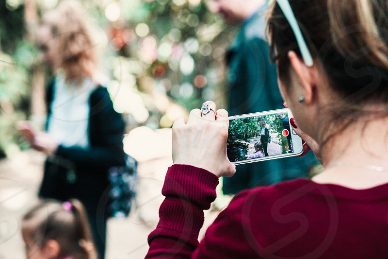 Young woman holding smartphone looking at phone screen recording a family trip photo