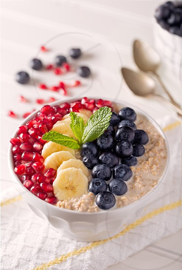 Cereal Bowl with Steel Cut Oats in Almond Milk Topped With Fruit and Mint Sprig photo