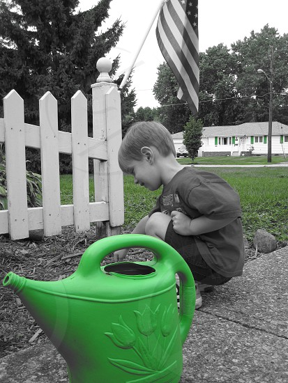 boy picking up green grass photo