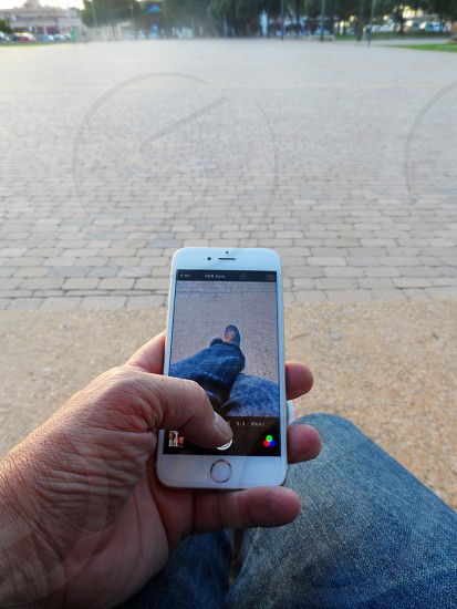 person holding white iphone 5S above blue jeans photo