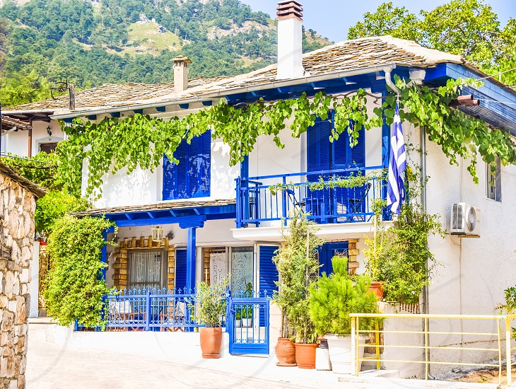 Greek Traditional House With Blue Windows And Doors  White Wall And Plants photo