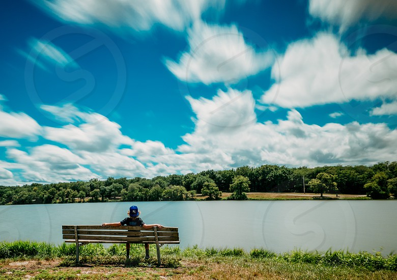 boy sitting on bench by the lake photo