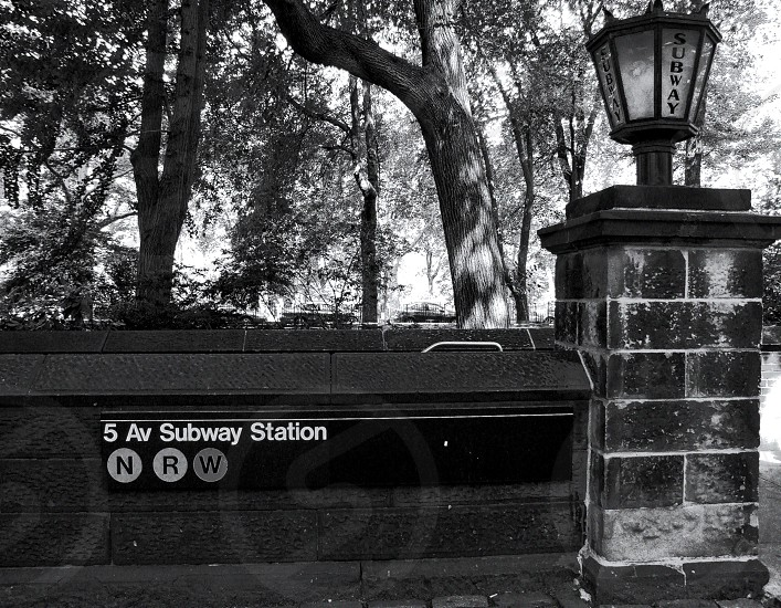 Black and white image of 5th Avenue subway entrance near Central Park in New York City. photo