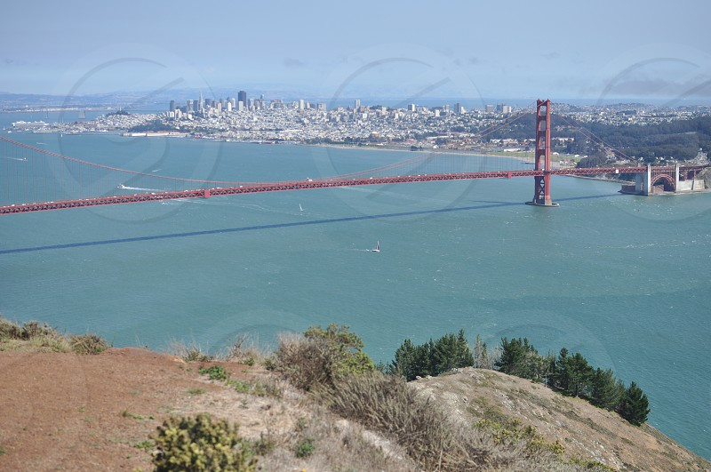 Golden Gate Bridge with cliff in the foreground and the city in the background photo