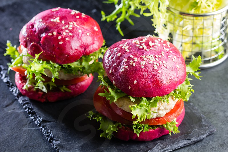 Colored purple beetroot burgers. Chicken burgers hamburgers with beetroot pink buns and vegetables photo