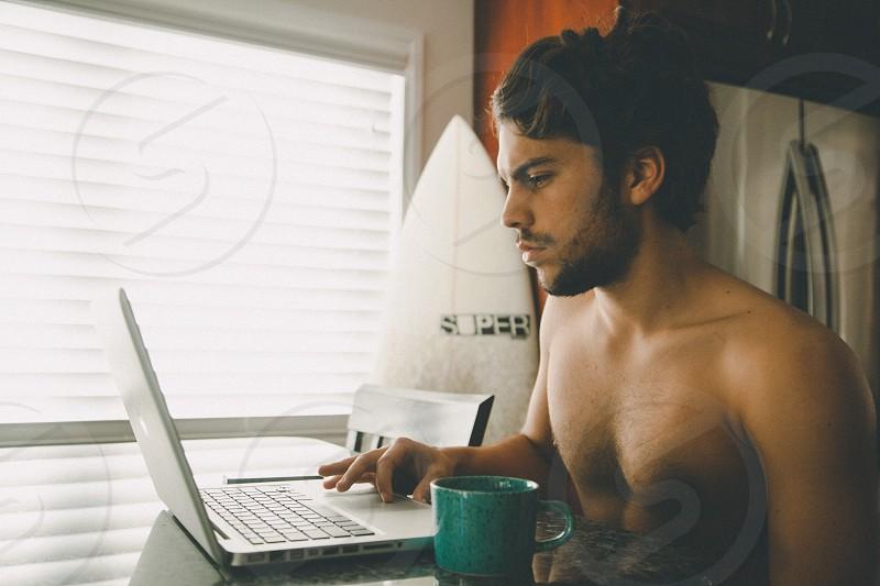 man top less using macbook pro photo