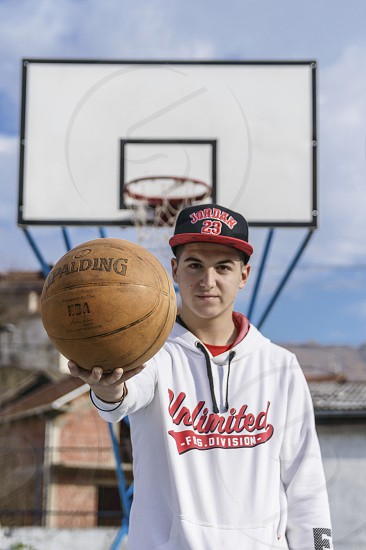 Boy standing in front of the hoop and holding a basketball ball photo