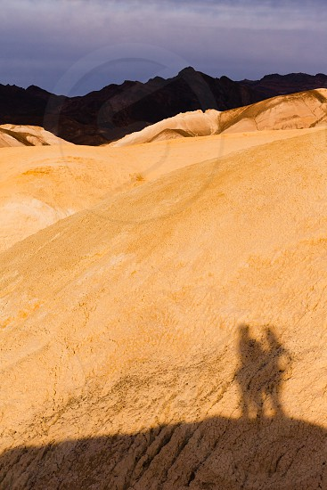 Shadow of active couple hiking in colorful shale mudstone badlands of Death Valley National Park California USA photo