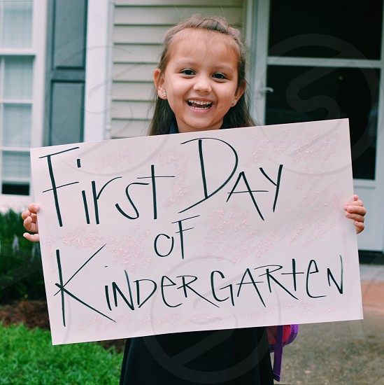 girl in school dress holding first day of kinder garten signage photo