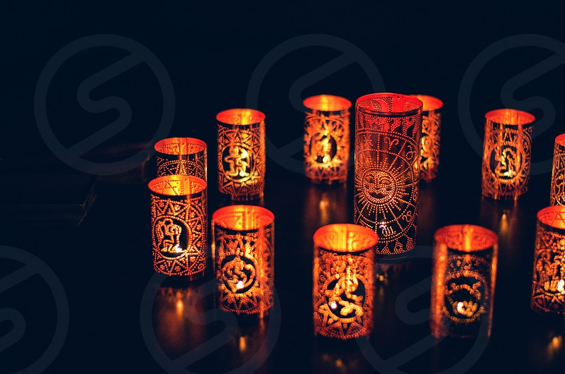 A set of copper zodiac candles at night. photo