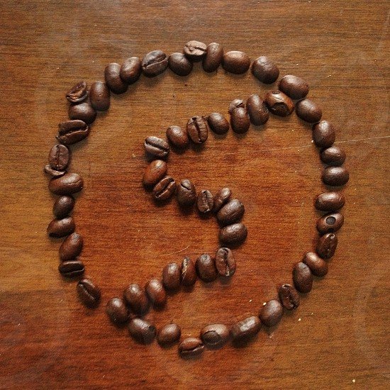Snapwire logo from espresso beans on oak table. photo