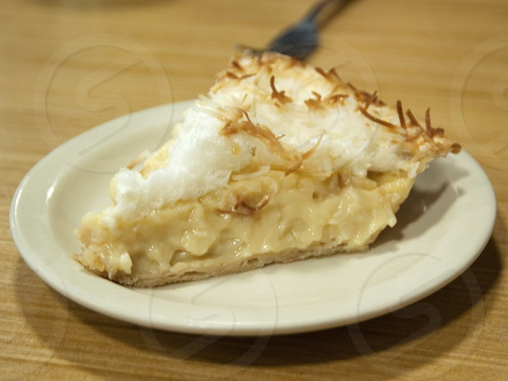 Coconut Meringue pie on white plate on wood tabletop photo