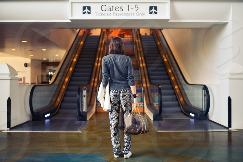woman in gray sweater and black and brown aztec pants facing gates 1 - 5 signage photo