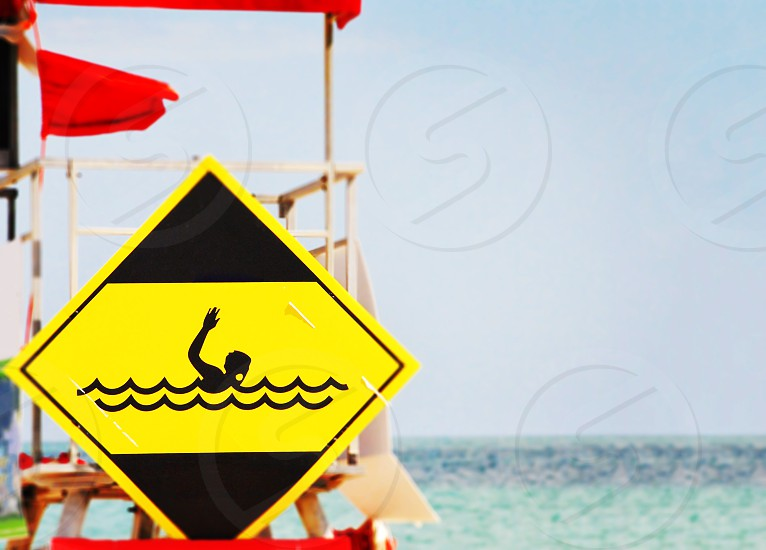 yellow danger signal depicting a drowning swimmer in the waves of a rough sea photo