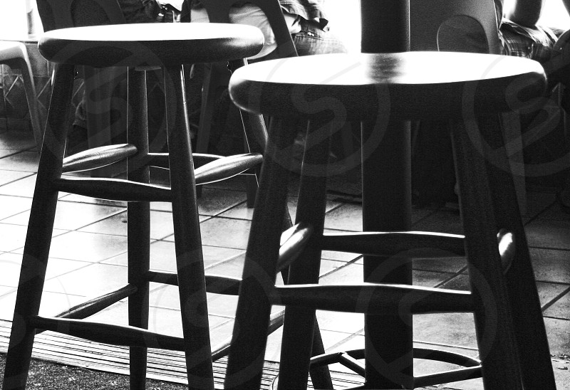 Close-up of black and white stools in a back lit restaurant interior photo
