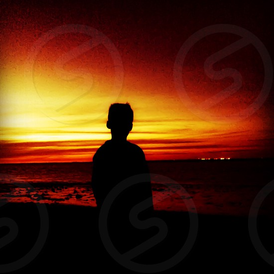 Boy looking out to sea at sunset  photo